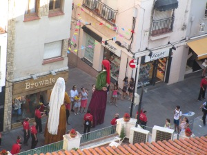 Los diablos (devils) de Sant Cugat parade through the street with los gigantes (giants)